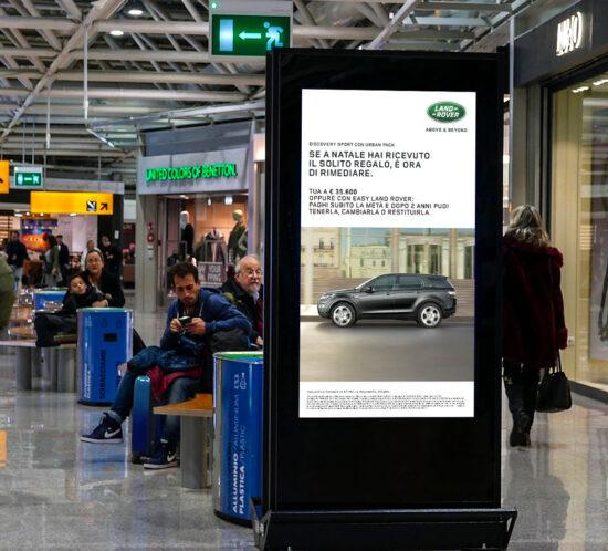 Schermo DOOH con Land Rover Discovery Sport Urban Pack in sala interna di aereoporto