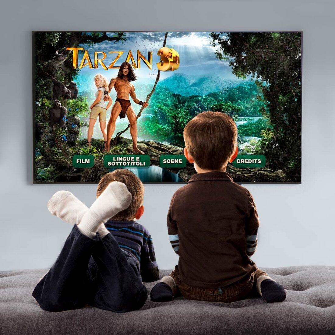 Due bambini seduti su un pouff guardano la grafica del Blu-Ray di Tarzan alla TV